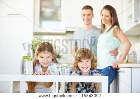 Happy family and two children in kitchen with fresh lime water