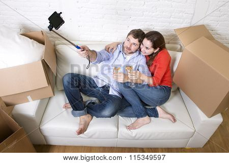 Happy Couple On Couch Having Fun Together Celebrating Champagne Toast Moving In A New House Taking S