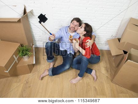 Happy Couple Sitting On Floor Celebrating Champagne Toast Moving In New House Taking Selfie Photo