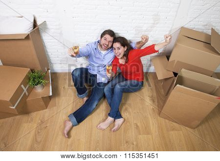 Happy American Couple Sitting On Floor Unpacking Together Celebrating With Champagne Toast Moving In