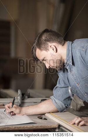 Carpenter Writing Down Measurements
