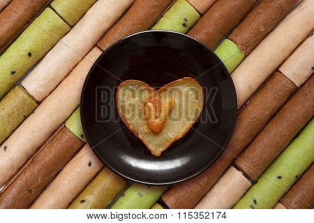 Heart Shaped Pancake With Letter V Inside On Dark Brown Plate