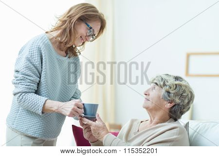 Care Assistant Helping Elderly Lady