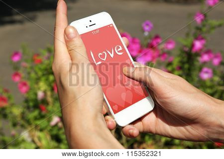Female hands holding smart mobile phone with romantic screensaver outdoors