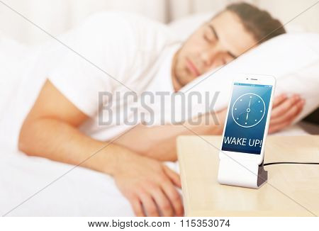 Young man waking up with mobile alarm clock