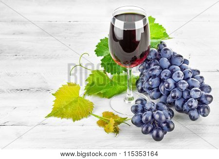 Glass red wine with cluster grapes on wooden board