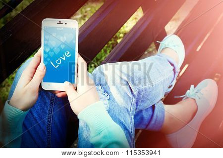 Young woman holding mobile phone with romantic screensaver