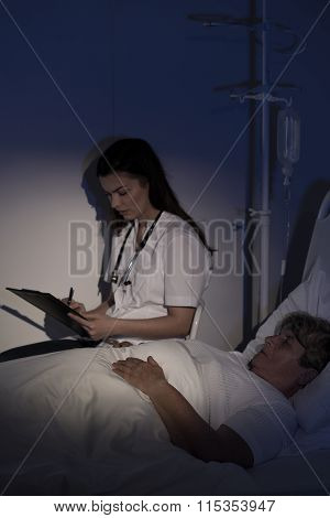Doctor Sitting By Elderly Patient