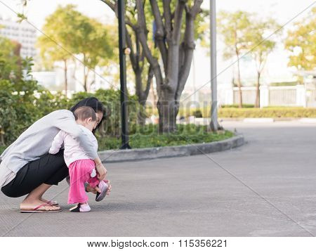 Asian Mother Help Toddler Wearing Shoes. While She Teaching Her Baby To Walk.