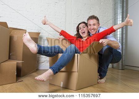 Happy American Couple Unpacking Moving In New House Playing With Wife Inside Carboard Box