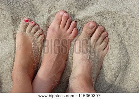 feet of father mother and daughter on the sand