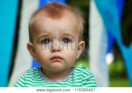 Serious Little Boy Portrait With Big Opened  Eyes On A Blue And