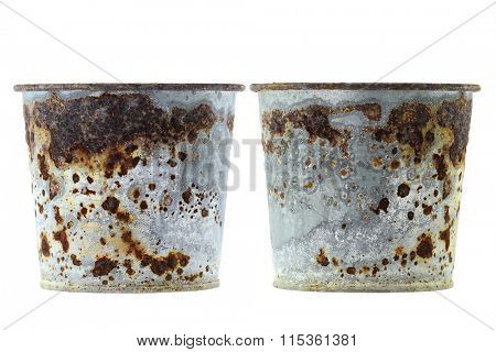 Rusty plant pots full of reddish brown flaky coating of iron oxide
