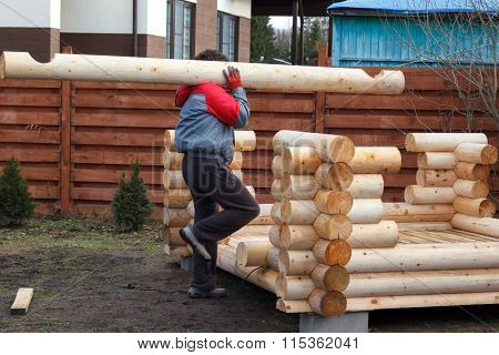 Man Carries Log To Build A Wooden Arbor