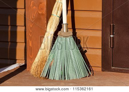 Broom And Besom Standing On Wooden Floor