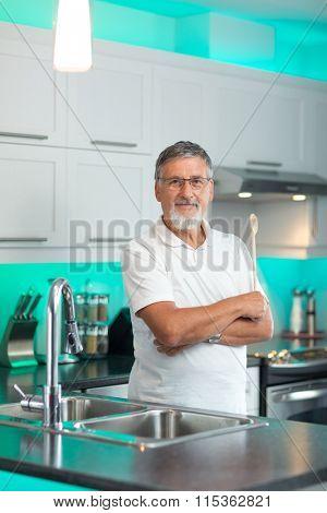 Senior man standing in his renovated, modern kitchen,