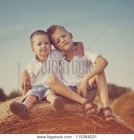 Two Little Brothers Sitting On A Haystack In Wheat Field On Warm