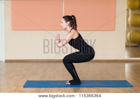 Woman Doing Squats And Holds Hands Namaste