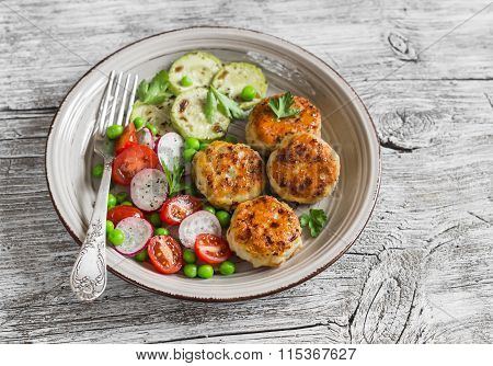 Chicken Cutlets,  Grilled Zucchini  And Fresh Vegetable Salad On Rustic Light Wood Background