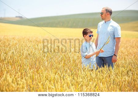 Happy father with little son walking happily in wheat field
