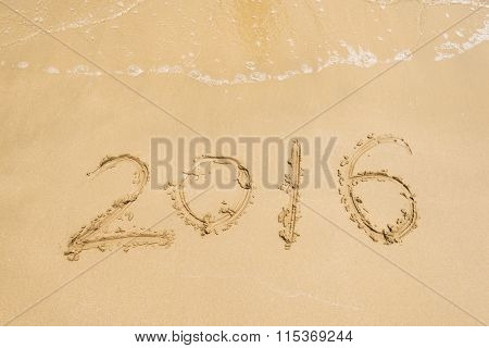 2016 written in sand, on tropical beach
