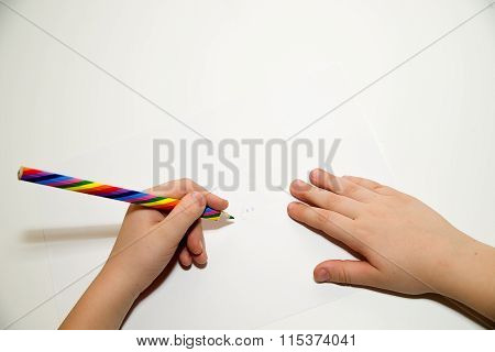 Kid's  Hands Holding A Pencil On Over White
