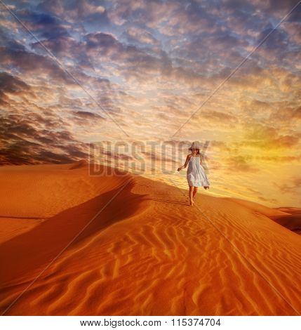 Little girl in white dress and hat walking down the sand dune in desert, at sunset