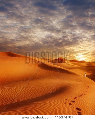 Sand dunes field at sunset and traces of a little girl walking along the desert