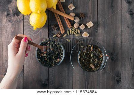 Woman Mixing Spoon Herbal Tea In Glass Jar