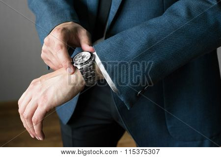 The photo of the man of the businessman in a jacket and a white shirt. The man looks at the watch