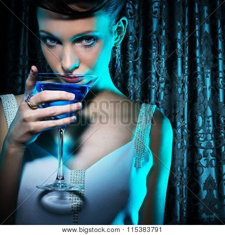 Beautiful woman with martini glass on damask curtain background
