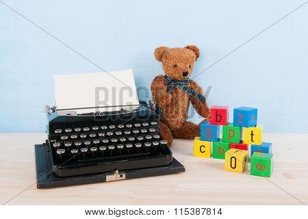 Two vintage bears and antique black typewriter