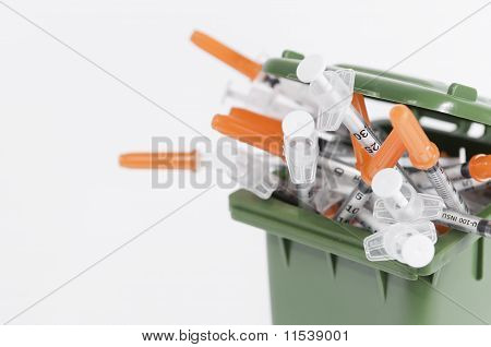 container full of hypodermic syringes