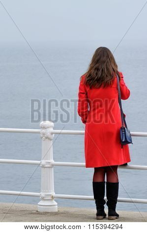 Woman In Red Coat With Black Boots Sitting In Front Of Seashore.young Woman With Red Coat Looking At