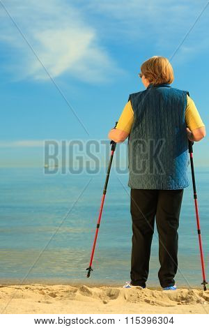 Active Woman Senior Nordic Walking On A Beach. From Behind