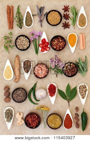 Spice and herb food seasoning sampler over natural hemp paper background.