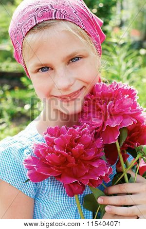 Little Girl With A Bouquet Of Pink Peonies.