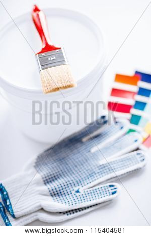 paintbrush, paint pot, gloves and pantone samples