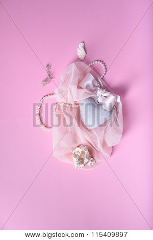 romantic card or invitation. Heart, shells, veil, silk ribbon over pink background. Top view.