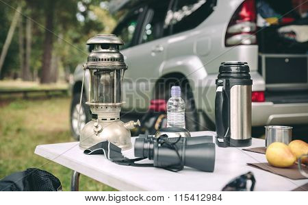 Oil lamp, thermos and binoculars over camping table