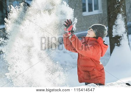 Teenage Boy Tossing Up Natural Snow In Frosty Winter Sunny Day Outdoors