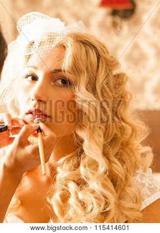 Expert stylist putting on lipstick for sexy caucasian bride closeup
