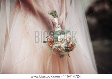 Beautiful Bride In A Pink Dress Holding A Bouquet And Hiding Under Her Veil Outdoors