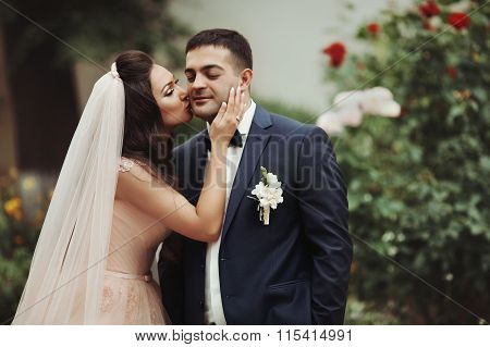 Sensual, Romantic Bride Kissing Handsome Groom On His Cheek With Flowers In The Background