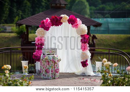 Romantic White Wedding Aisle Archway With Rose Petals, Flowers And A Decorated Chest. Lake In The Ba