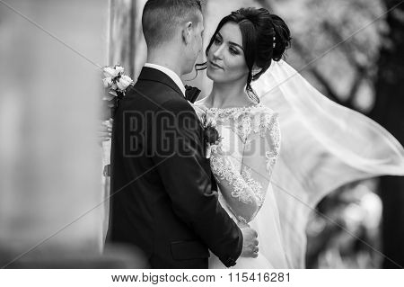 Happy Newlywed Brunette Bride Hugging Handsome Groom Near Old Wall Closeup B&w