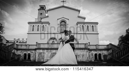 Happy Newlywed Couple Hugging In Front Of Old Baroque Church In Lviv, B&w