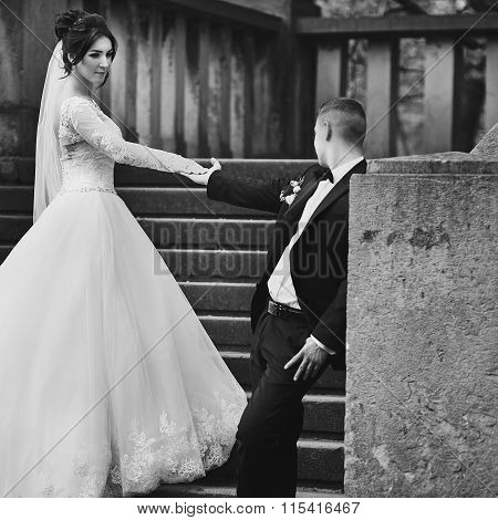 Gorgeous Brunette Bride And Confident Groom Holding Hands On Old Stone Stairs B&w
