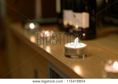 Candles And Blurred Bottles Of Wine