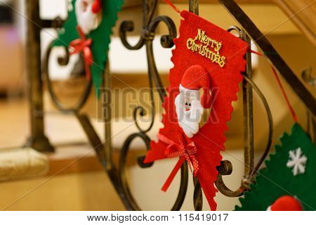 Home Christmas Decoration With Santa Claus Face Hanging On A Fence With Merry Christmas Writing